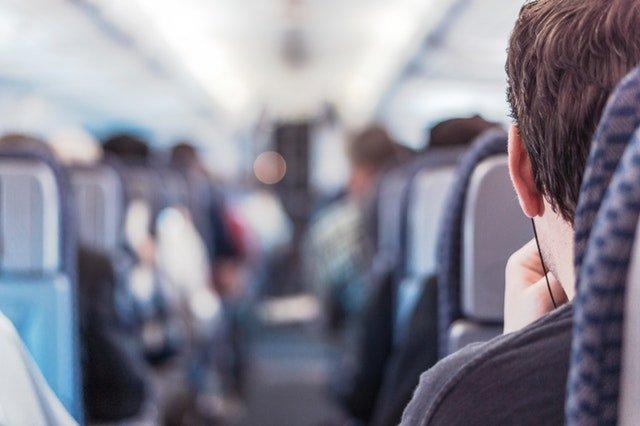 Chlap sediaci v lietadle so slúchadlami na ušiach
