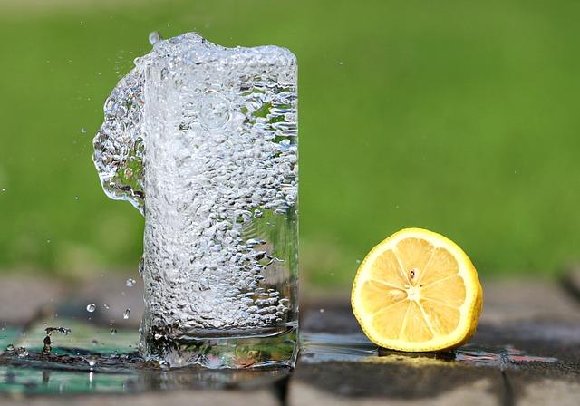 Pohár s bublinkovou vodou, vedľa ktorého leží polovica citrónu.jpg