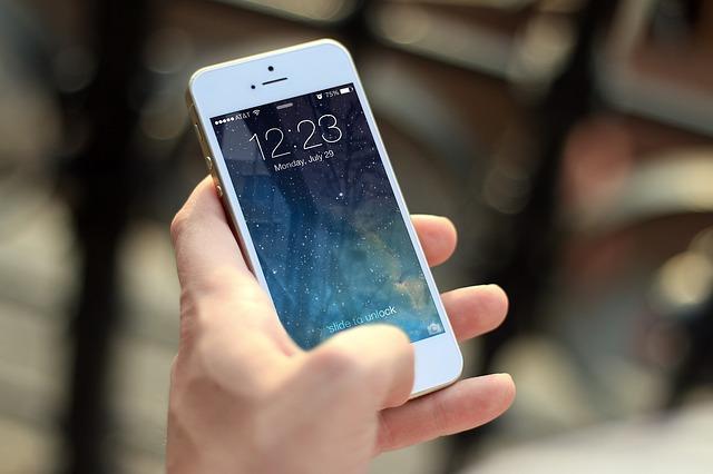 Ruka drží biely iPhone.jpg