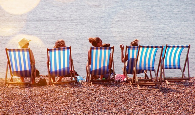ľudia oddychujúci na ležadlách pri mori