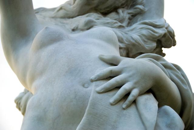 Socha ženy plnších tvarov, ktorá sa drží za brucho