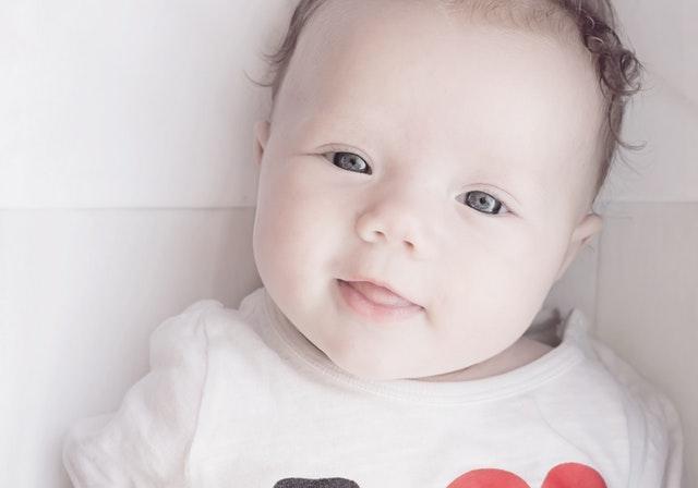 Bábätko ležiace v detskej postieľke sa usmieva