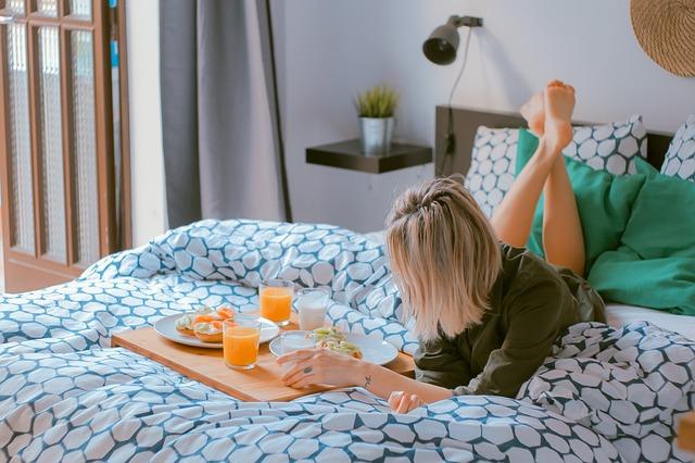 Žena leží na posteli s farebnými vzorovanými obliečkami a má pri sebe raňajky.jpg