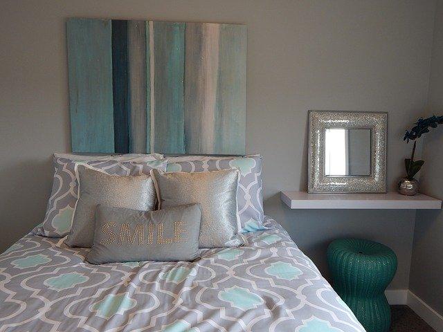 Jednoducho zariadená spálňa s posteľou, modrým obrazom a nočným stolíkom.jpg