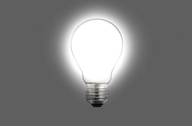 Rozsvietená biela žiarovka na sivom pozadí