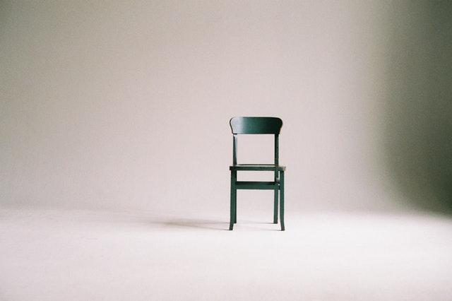 Čierna stolička v bielej prázdnej miestnosti.jpg