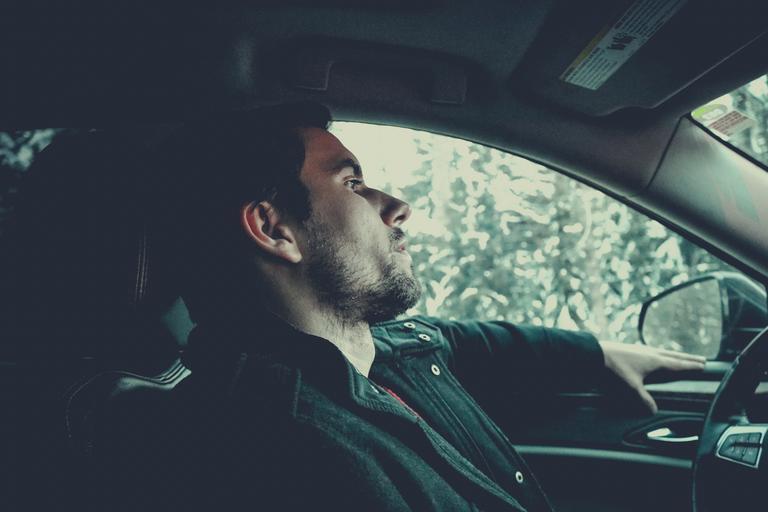 Muž s čiernymi vlasmi sedí v aute a je zamyslený.jpg