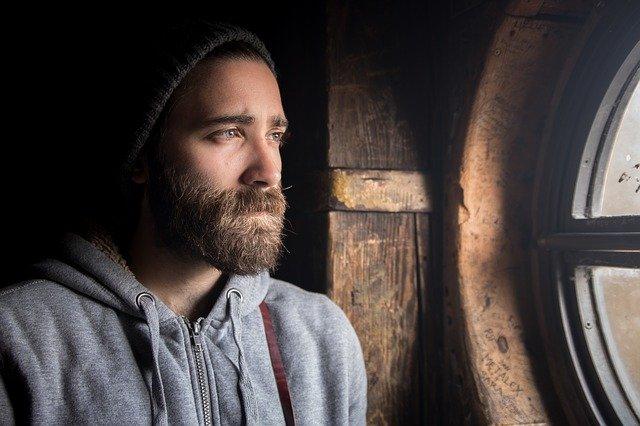 Smutný muž hľadí do okna, mladý, brada