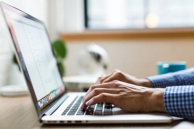 Muž v kockovanej košeli píše na počítači